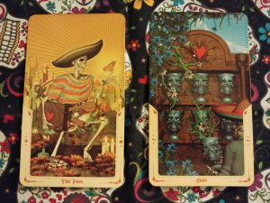 Two Tarot cards: The Fool- 0 and Seven of Cups, from the Santa Muerte Tarot deck
