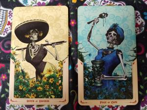 Two Tarot cards: Queen of Swords and Page of Pentacles, from the Santa Muerte Tarot deck