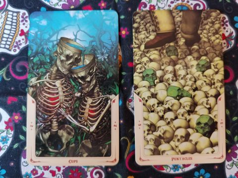 Two Tarot cards: Two of Cups and Five of Pentacles from the Santa Muerte Tarot deck.