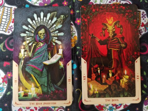 Two Tarot cards: The High Priestess- II and The Devil- XV from the Santa Muerte Tarot deck