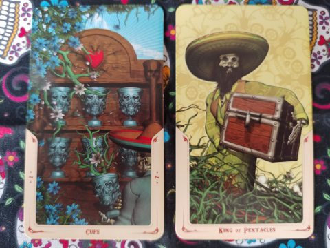 Two Tarot cards: Seven of Cups and King of Pentacles from the Santa Muerte Tarot deck