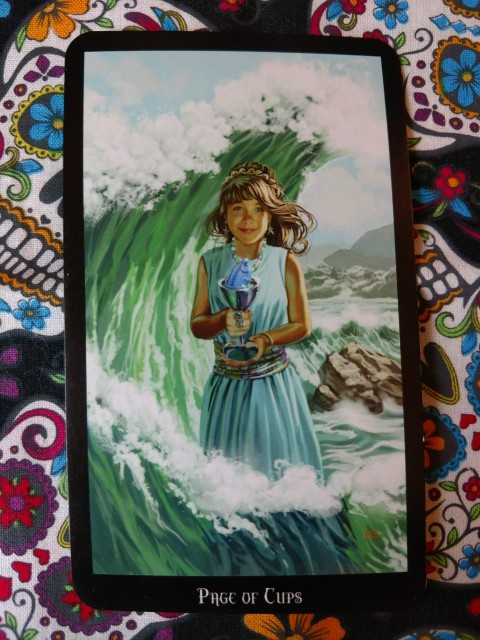 Page of Cups, from the Witches Tarot. Depicts a young girl in aqua blue dess holding a cup, ocean waves behind her. Inside the cup, a small fish peeks out.